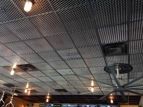 Expanded metal ceiling tiles with diamond holes are installed on the ceiling where lights and fans are installed in the basement.