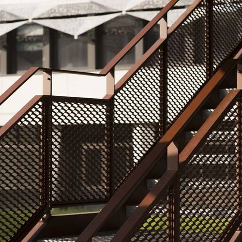 Raised expanded metal sheets with diamond holes as railings are installed on the stairs outdoors.