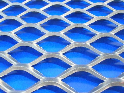 A piece of galvanized expanded metal sheet with raised surface and diamond holes.