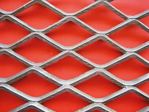 Fattened carbon steel expanded metal with diamond holes on red background.