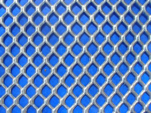 Heavy duty galvanized expanded metal sheet with flattened surface and hexagonal holes.