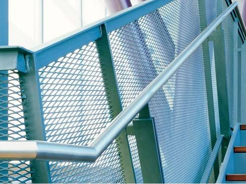 Expanded metal stair railing with blue surface and diamond holes in public building.
